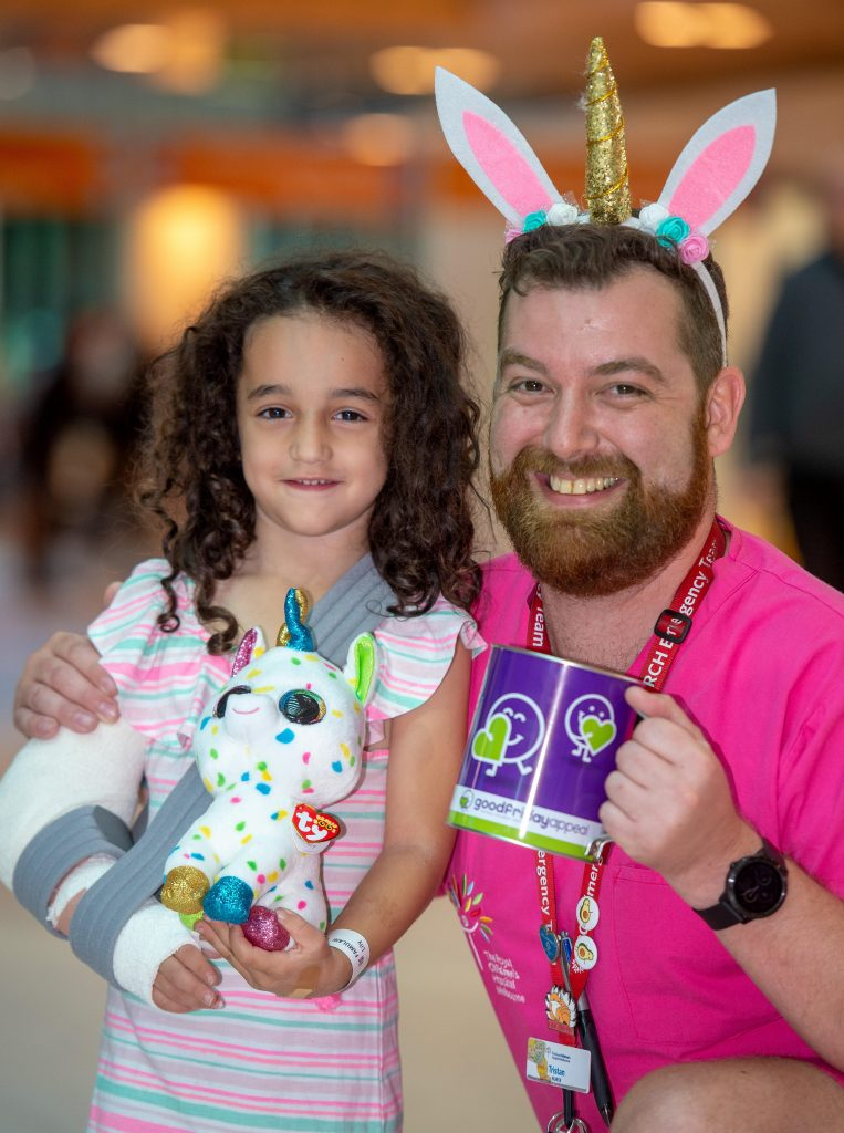 Good Friday at the RCH. Registered Nurse Tristan Dolling rattles a tin with Lily Famulari (5) who has broken her arm. Picture: Jay Town