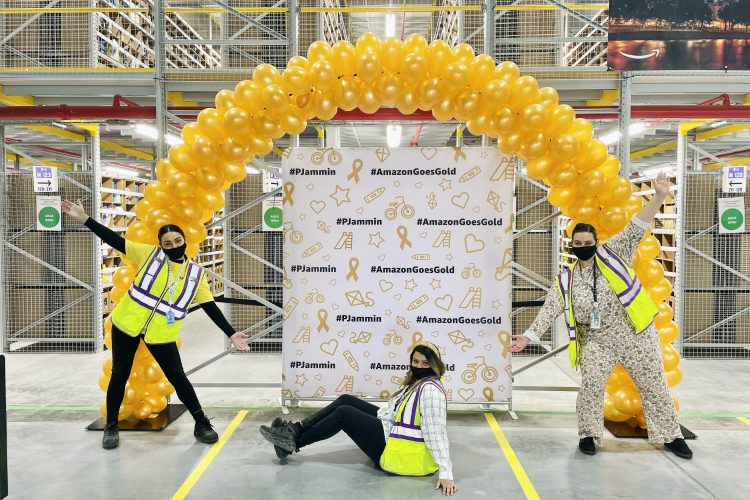 Three Amazon staff in front of a balloon arbor in their pj's